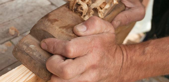 ein Tischler hobelt, in Großaufnahme nur der Hände