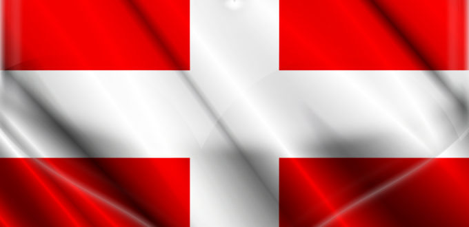 die schweizer Fahne, ein weißes Kreuz auf rotem Grund, darüber liegt ein angedeutetes durchsichtiges Herz