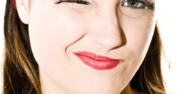 junge Frau schaut skeptisch in die Kamera, Porträt, rotes Haarband