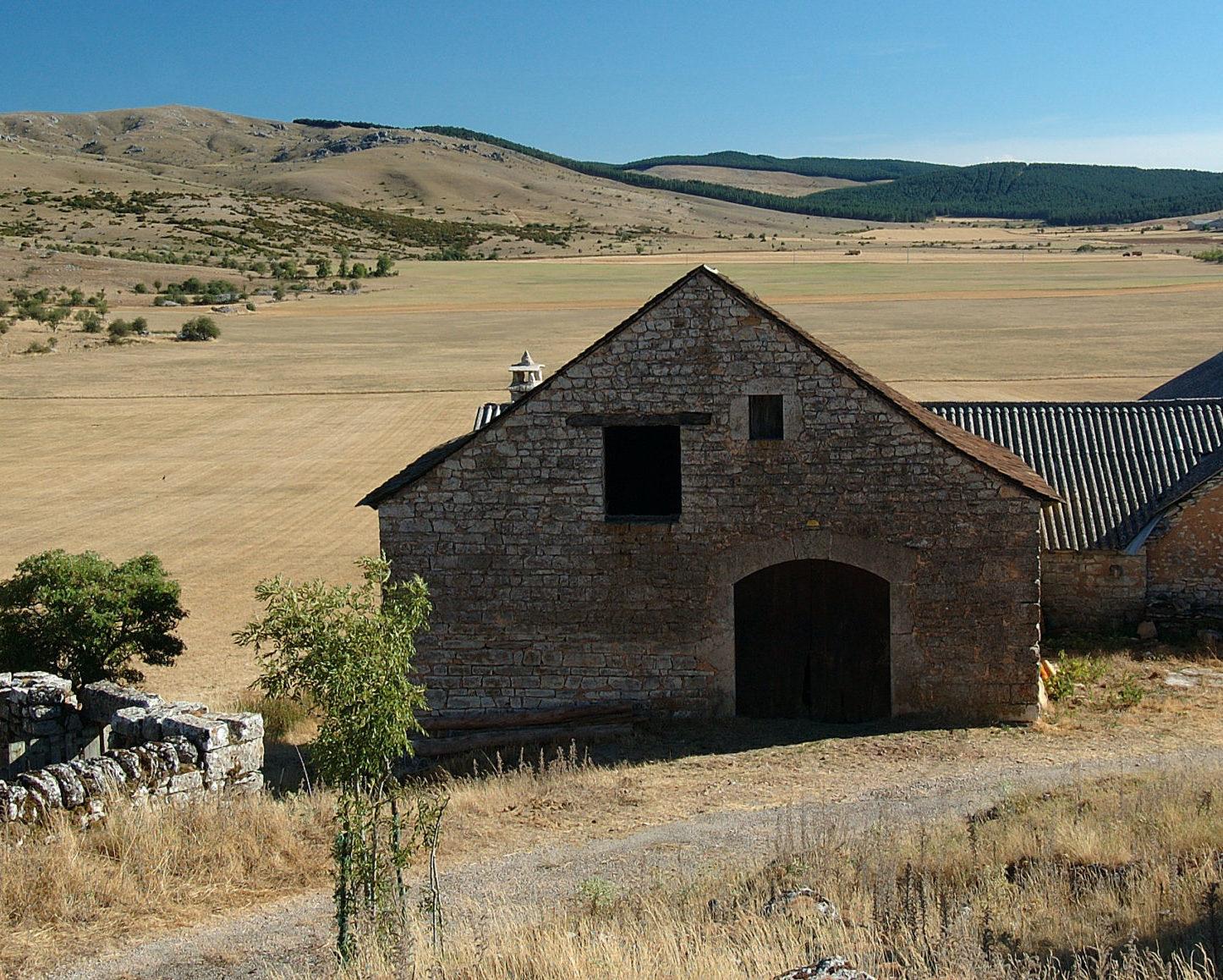 ein altes Bauernhaus mit Nebengebäuden und Steinmauer, im Hintergrund eine verödete weite Landschaft