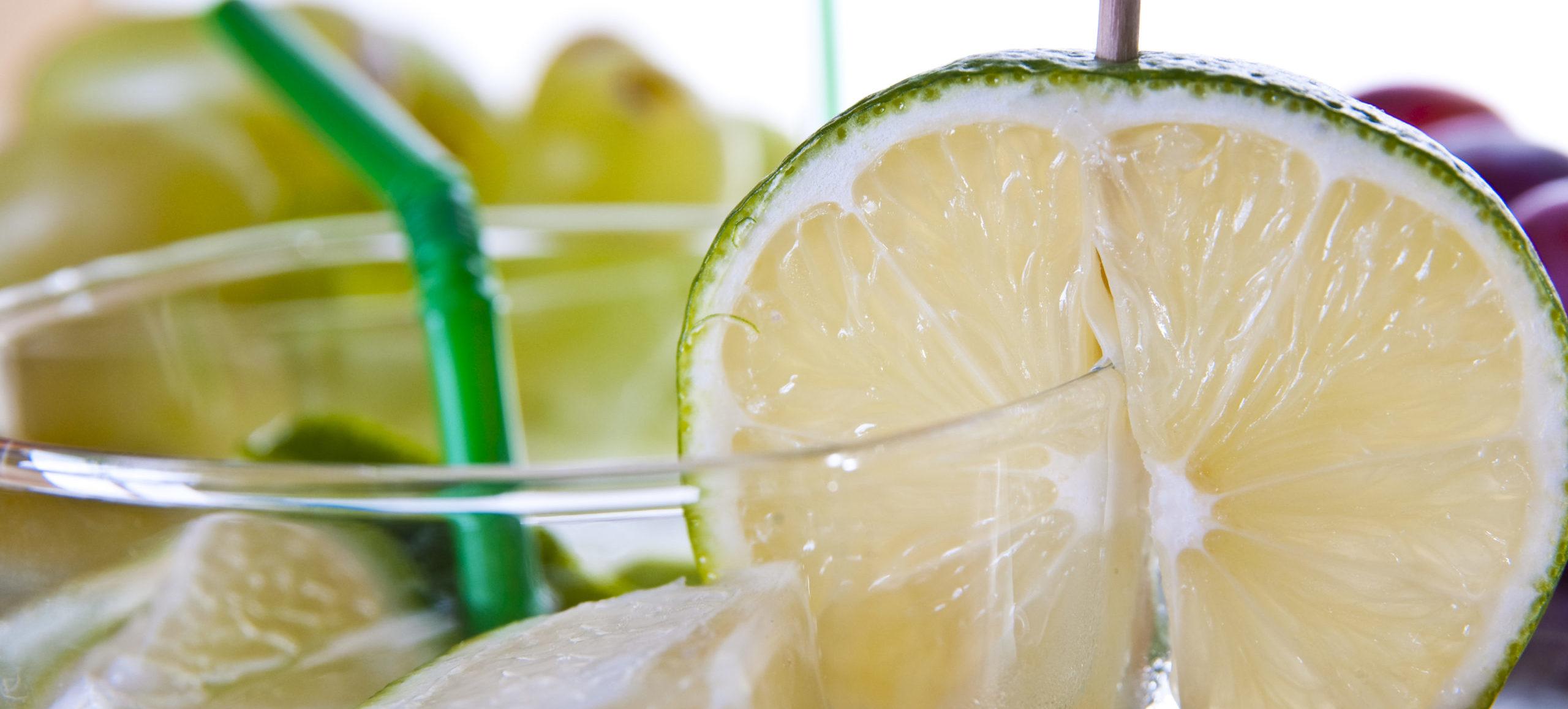 Sommer Drinks in groß eine Limette auf einem Glasrand, in groß auch ein Trinkhalm