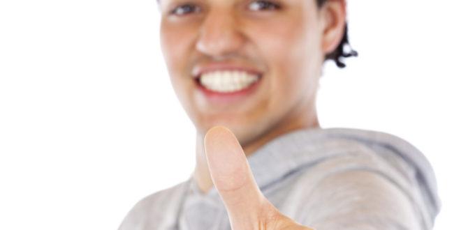ein junger Mann hält seinen erhobenen Daumen in die Kamera und grinst dabei, ohne Hintergrund