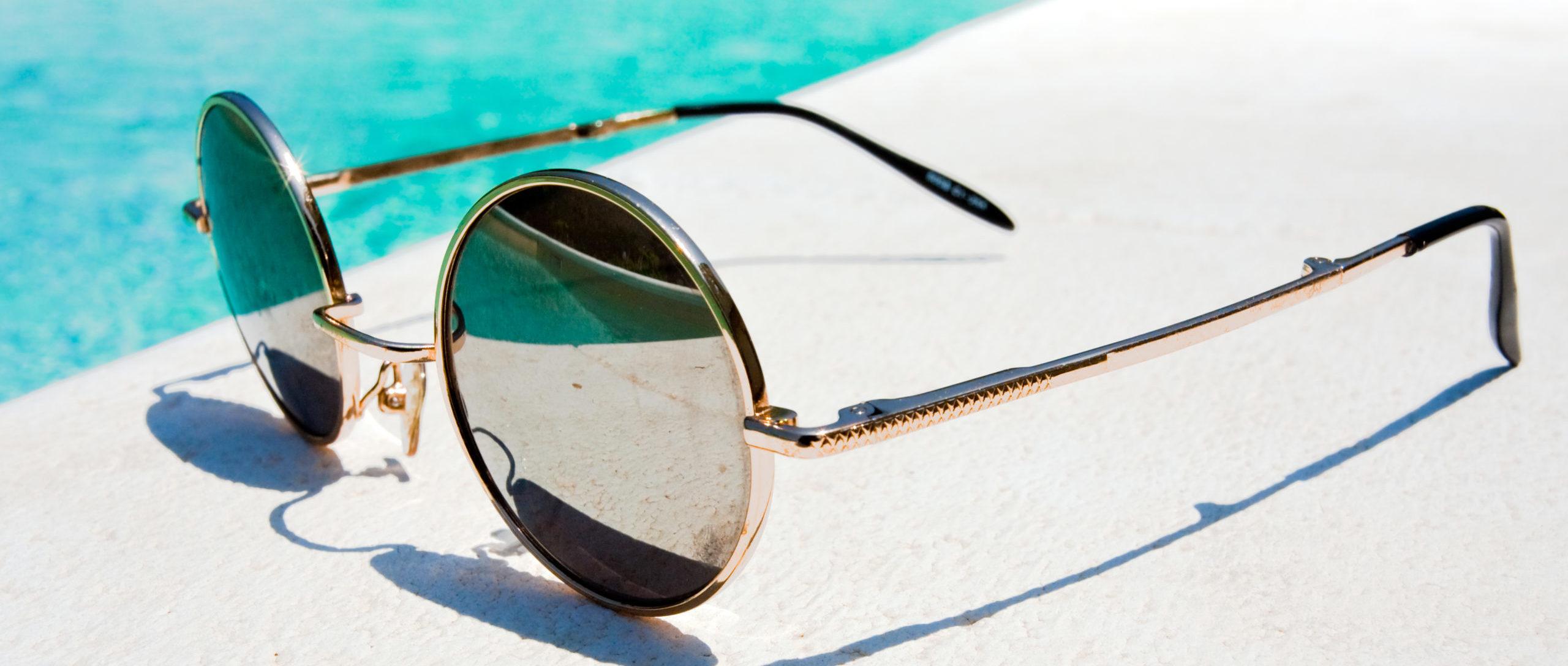 eine Sonnenbrille in groß, liegt vor Schwimmbadrand