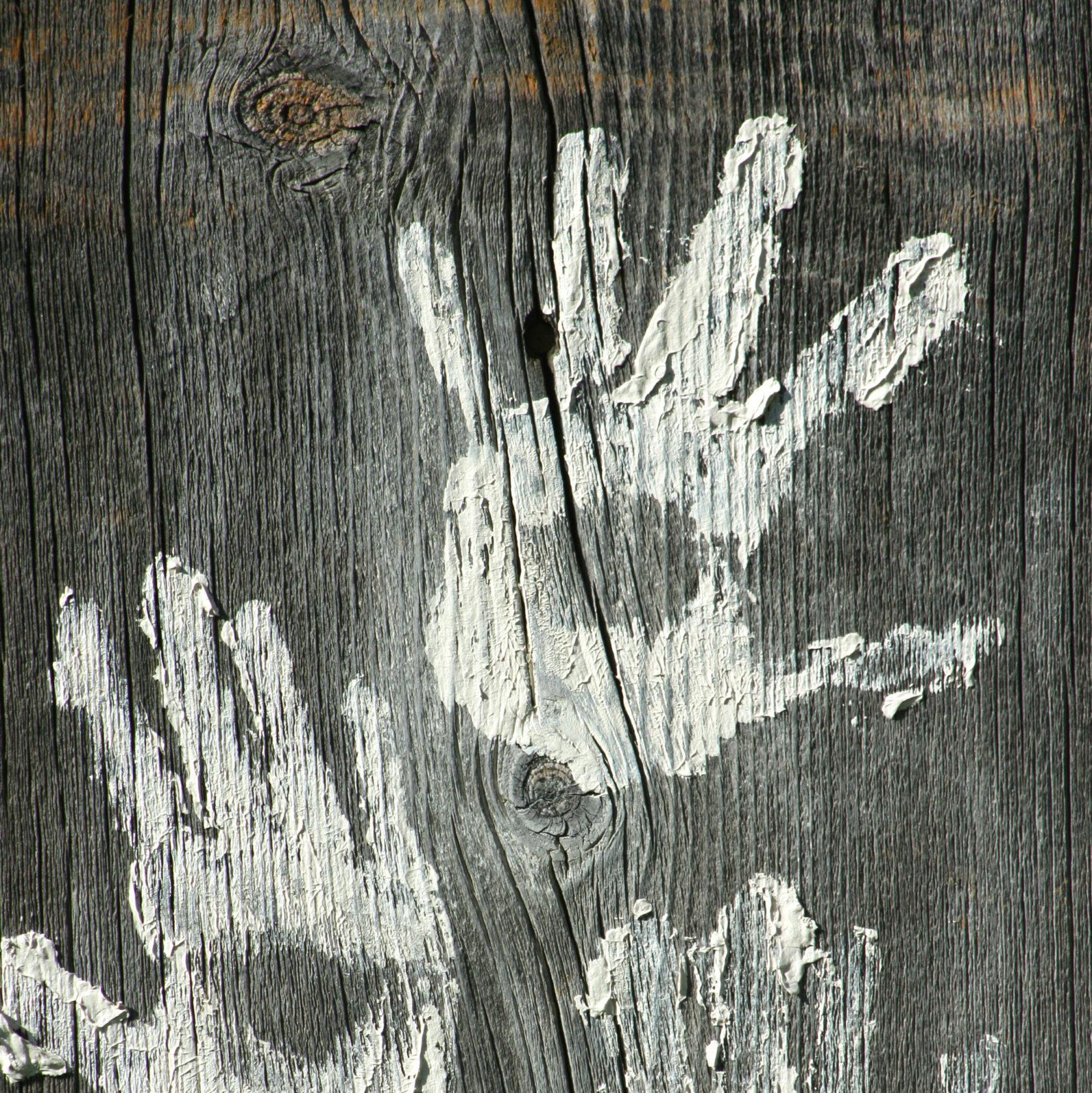 Lehm-Handabdrücke auf ungehobeltem Holz