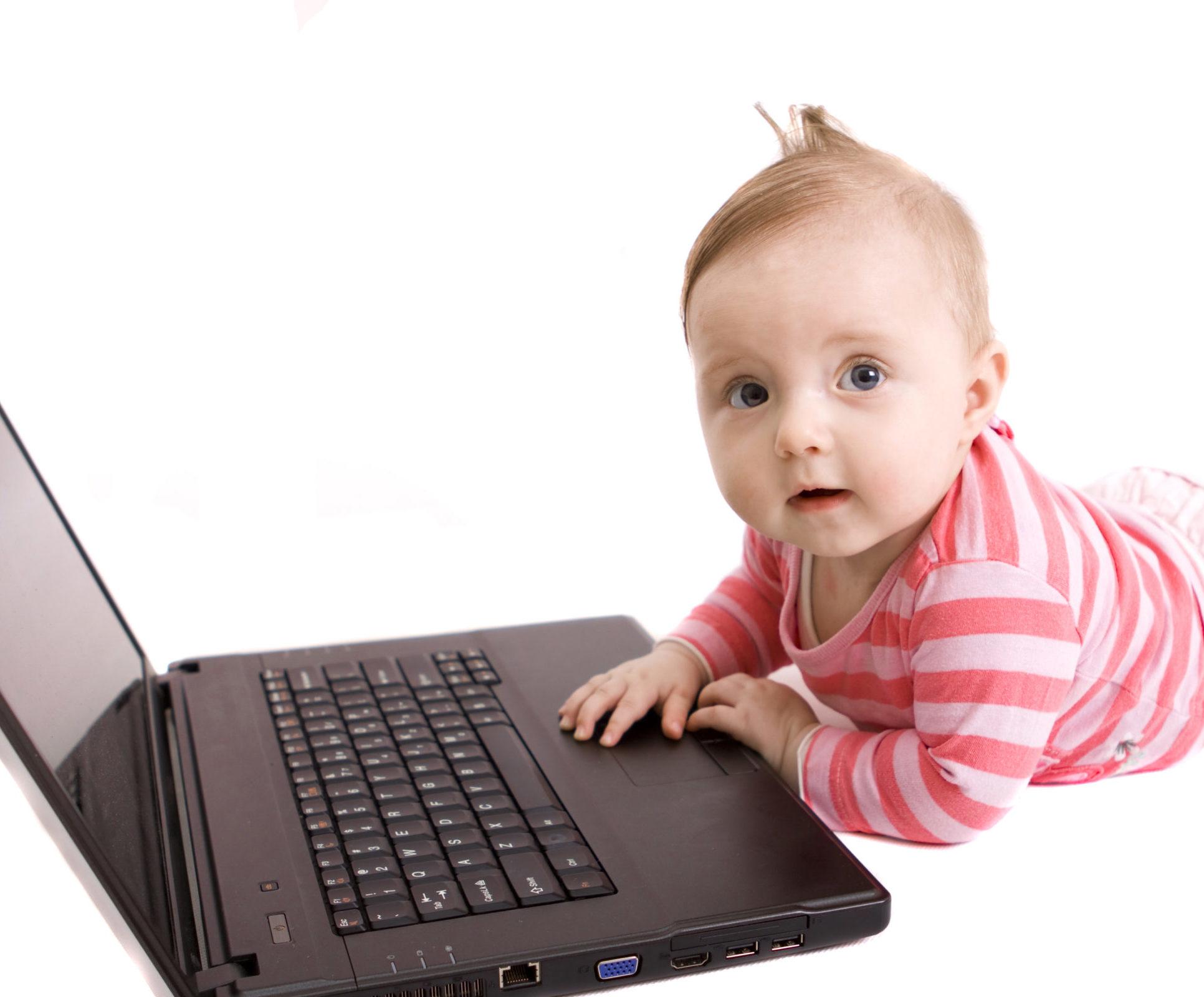 ein auf dem Bauch liegendes Baby hat eine Hand auf dem Laptop, der vor ihm am Boden aufgeklappt steht, schaut in die Kamera