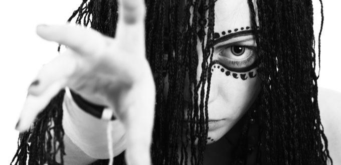 eine schwarzweiss Grossaufnahme einer modernen Hexe, die mit einer Hand fordernd den Betrachter greifen will