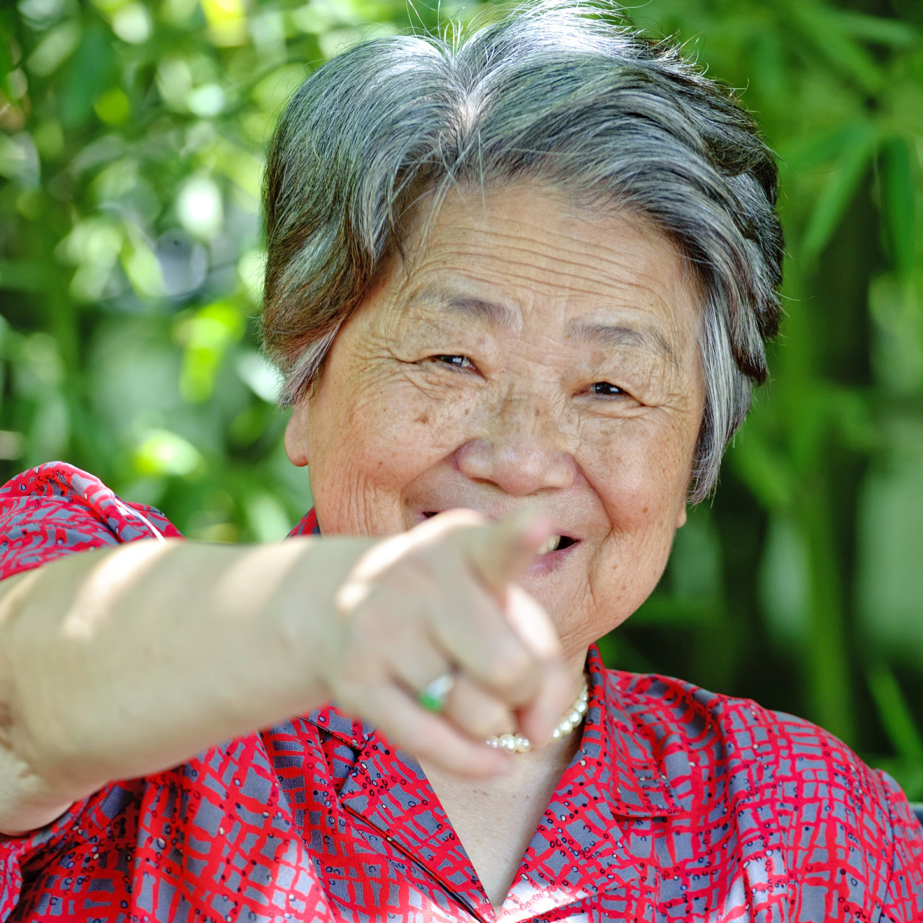 eine alte Frau zeigt mit großem Lachen mit der gestreckten Hand und dem Zeigefinger voll in die Kamera