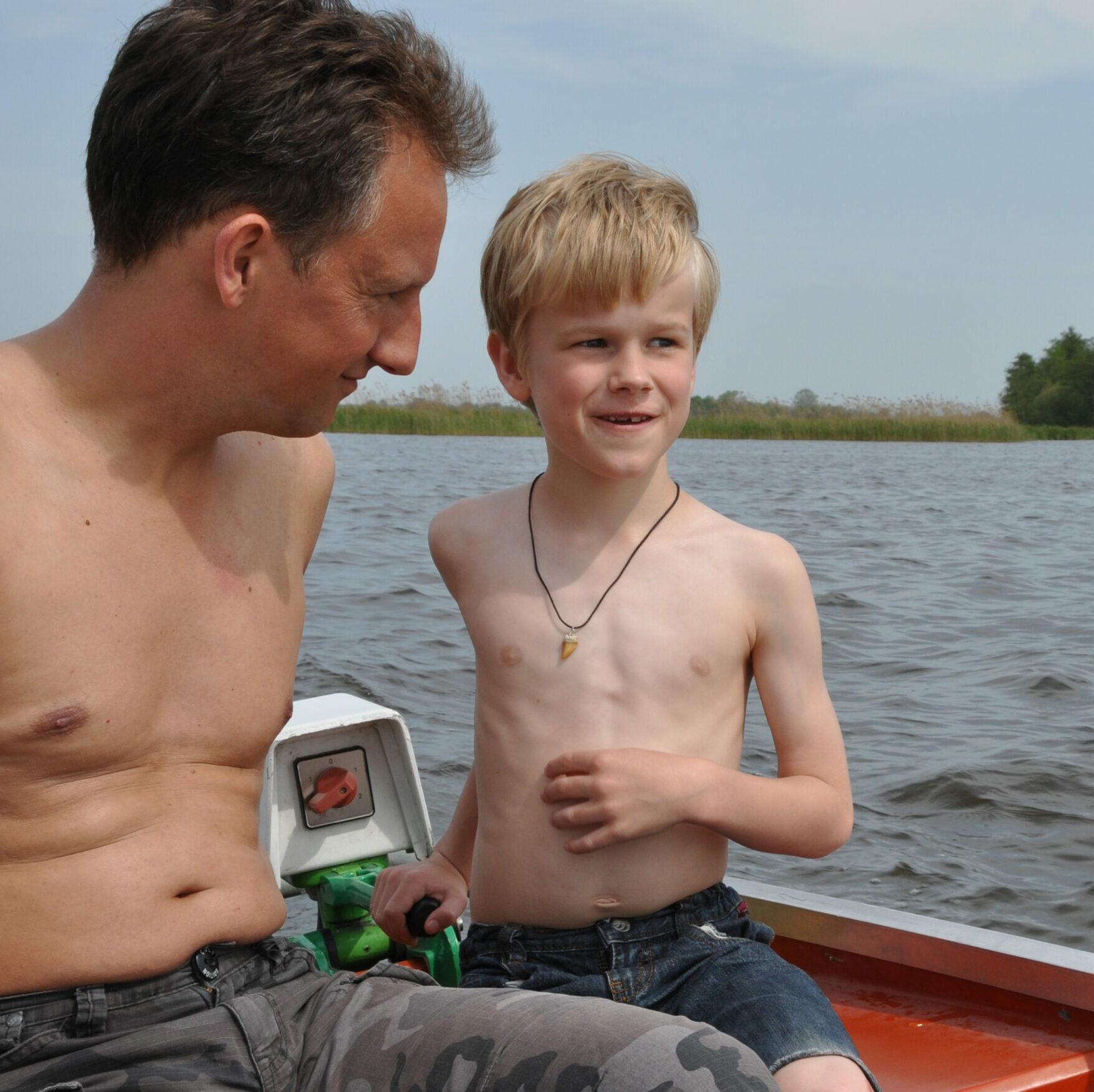 ein circa neunjähriger Bub wird von einem Mann neben ihm mit Anerkennung angeschaut, beide steuern grad ein Boot