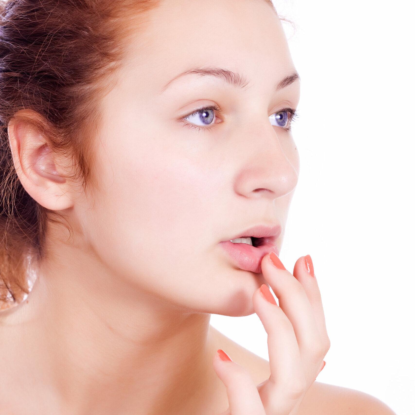 eine nackte Frau schaut mit sensiblem und abwesendem Blick ins Nirgendwo, Der eine Finger berührt sanft eigene Lippen