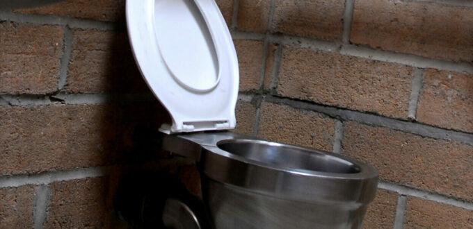 eine moderne Toilette ohne Spülkasten, mit Waschbecken daneben, alles aus Chrom ausser die weisse Klobrille