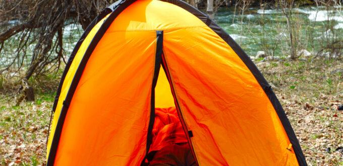 ein oranges Zelt, eine Person liegt drinnen und die Beine schauen heraus, Waldhintergrund