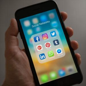 ein Handybildschirm voller Social Media Icons in groß wird von einer Hand gehalten, grauer Hintergrund