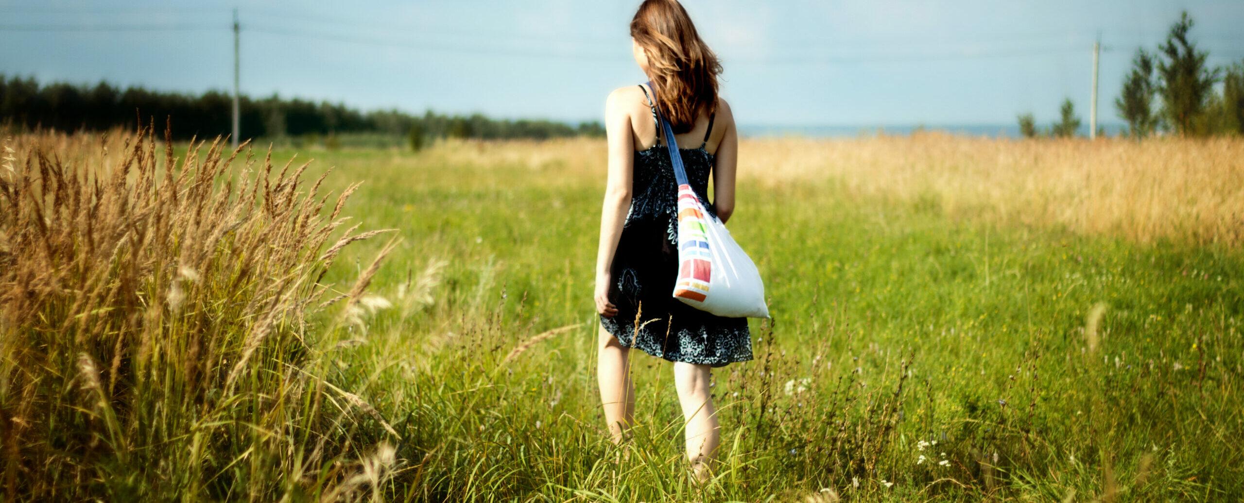 Frau im Sommergewand geht im Herbstfeld