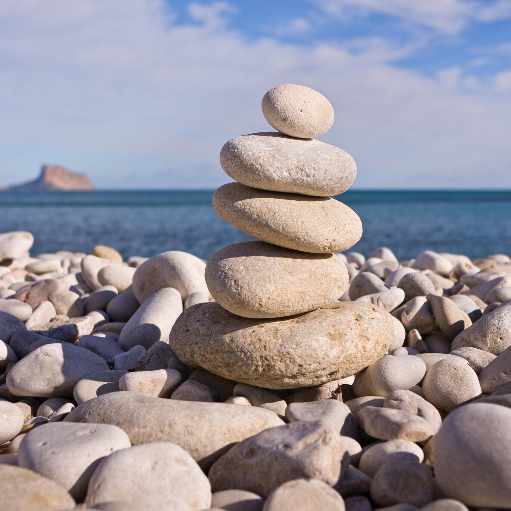 am Strand voller Steine steht ein Turm mit 5 aufeinandergeschlichtete Steinen im Vordergrund, Hintergrund das Meer und blauer Himmel